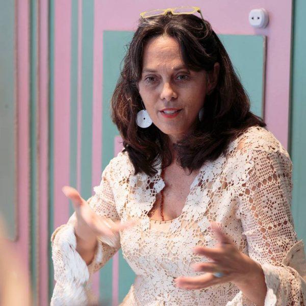 L'artiste Annalee Davis, habillée de blanc, parle en utilisant une gestuelle corporelle orientée vers la caméra avec le regard légèrement vers le bas.