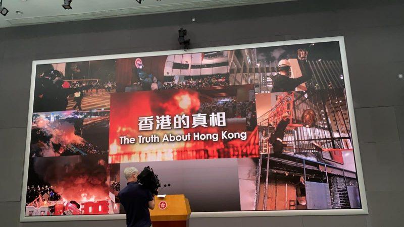 """Au centre du poster """"La vérité sur Hong Kong"""". Ce panneau est entouré d'images d'incendies, de pauvreté et de répression policière."""