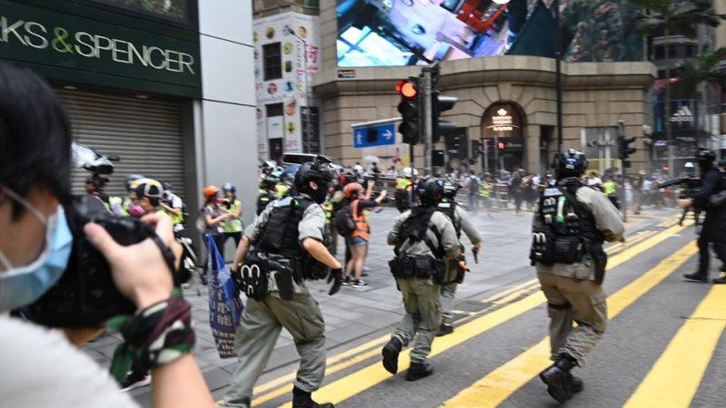 On distingue des policiers chargeant les manifestants dans les rues de Hong Kong. Les policiers tirent des balles de défense au poivre. En tout premier plan, un photographe, portant un masque de protection faciale, immortalise les scènes de chaos.