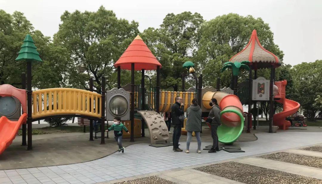 Au premier plan, un enfant, portant un masque facial, court sur une aire de jeux où se trouvent différents types de toboggans. Trois adultes sont présents à ses côtés.