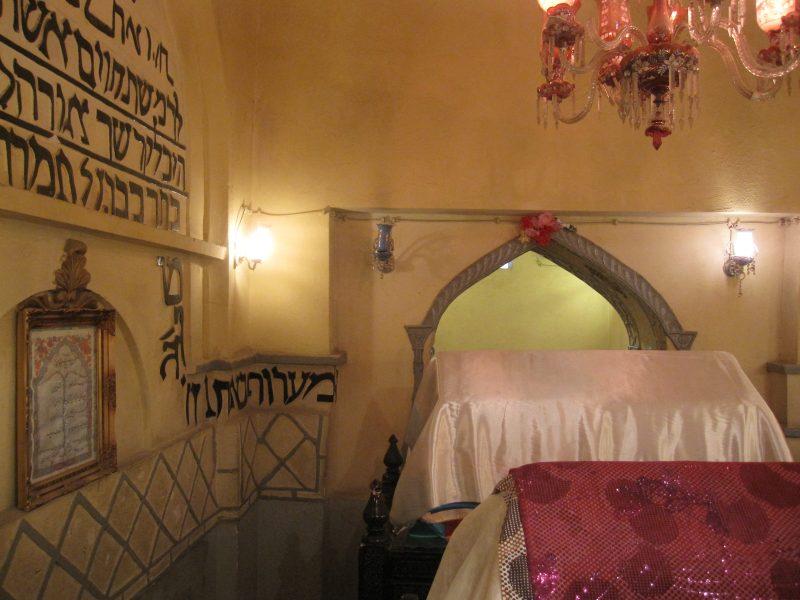 L'intérieur du tombeau d'Esther, éclairé par un chandelier. Deux tombes sont recouvertes d'un drap. Sur le mur de gauche, on peut lire des inscriptions en hébreu.