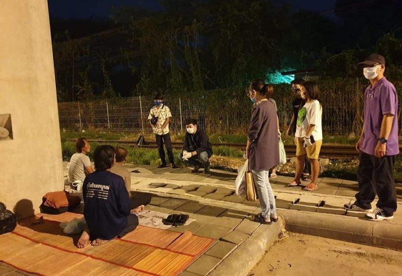 Les visiteurs se tiennent à distance, portant masques et gants, tandis que les personnes sans-abri leur font face, assises sur une natte.
