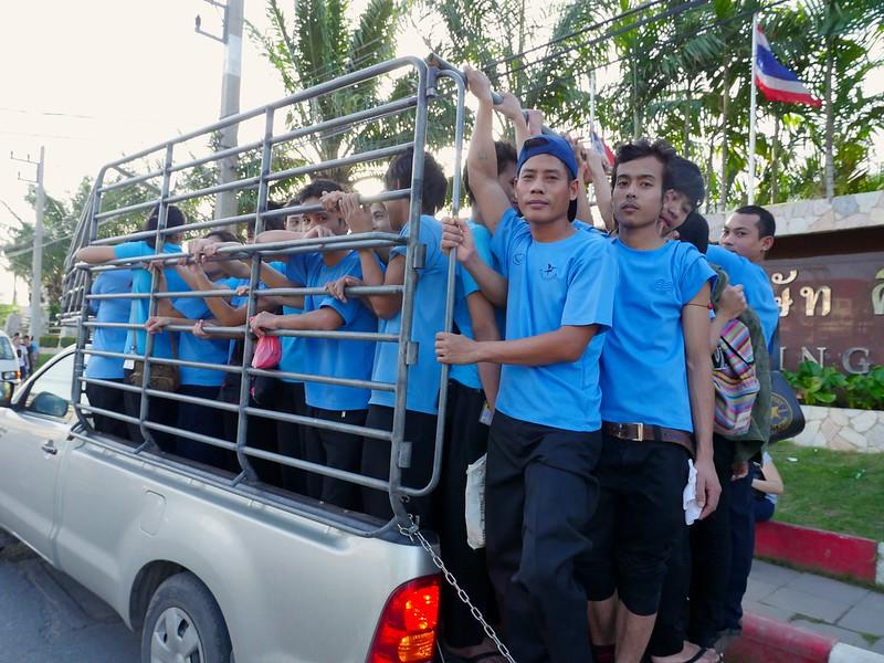 Un groupe d'ouvriers en uniforme se tient à l'arrière d'un pick up. On aperçoit le drapeau thaï derrière eux.