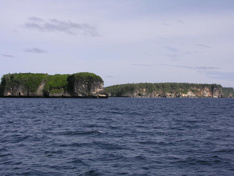 On distingue une mer bleue et calme en premier plan et l'île de Vava'u en arrière plan. L'île s'étend sur toute la longueur de la photo. On découvre des falaises et de la verdure sur l'île, sous le soleil.