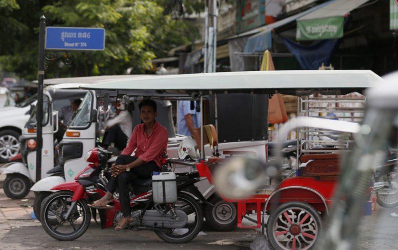 Plusieurs tuk tuks sont garés dans une rue de Phnom Penh. Un chauffeur attend les clients, assis dans son véhicule.
