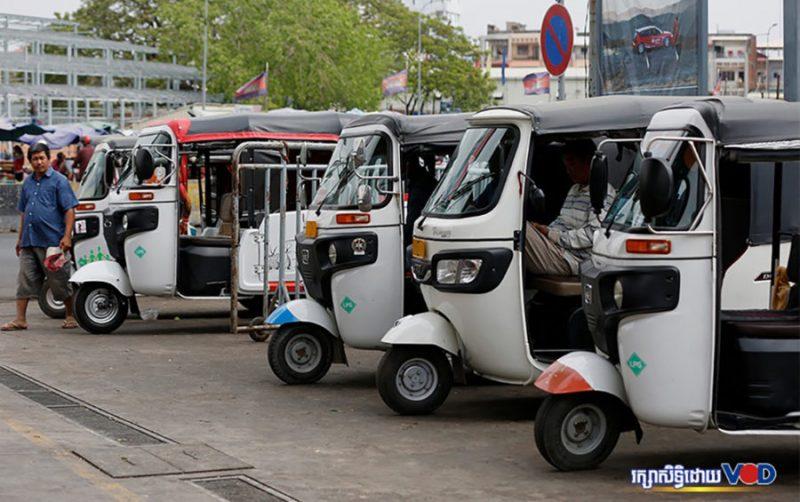 les « tuk-tuks » alimentés au GPL stationnent en ligne, les chauffeurs attendent les clients à Phnom Penh.
