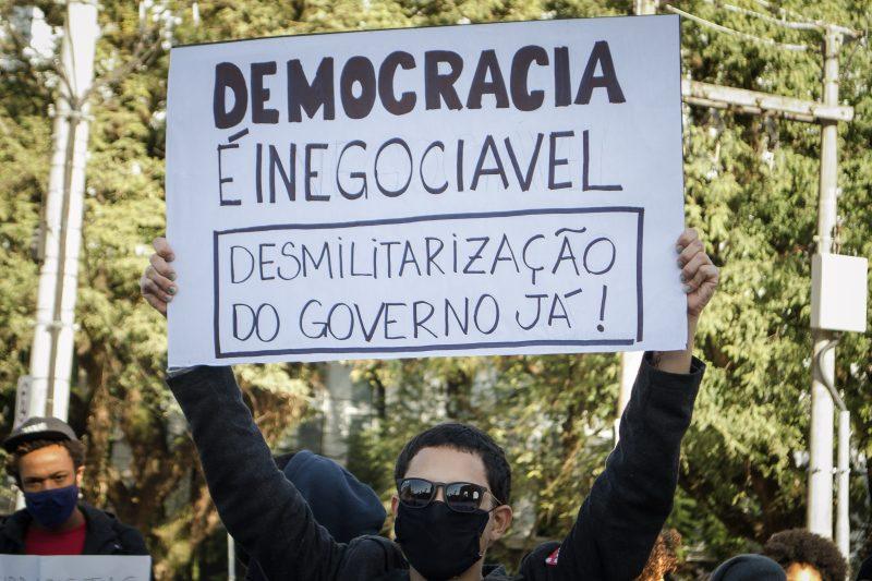 Un manifestant brésilien en masque et lunettes de soleil brandit une pancarte réclamant la démilitarisation du gouvernement.