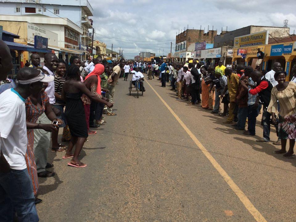 L'arrivée de la course dans une rue encadrée par deux rangs de personnes accueillant le premier participant en fauteuil roulant