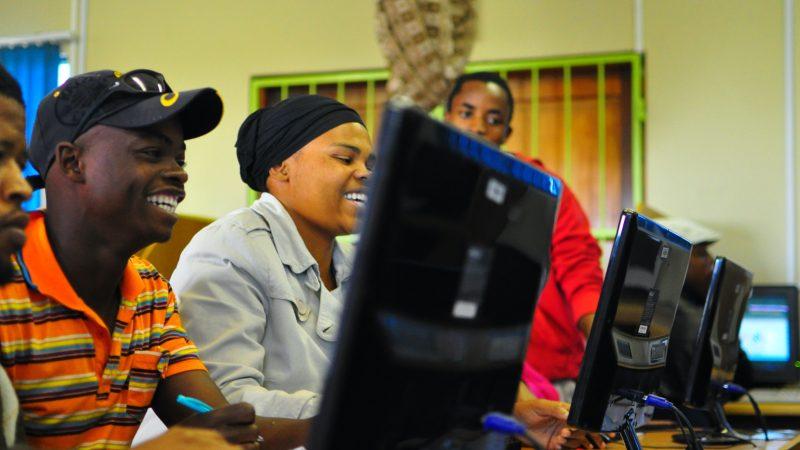 Un groupe de jeunes sud-africains suivent une formation sur ordinateur à la bibliothèque de Masiphumelele en Afrique du Sud.