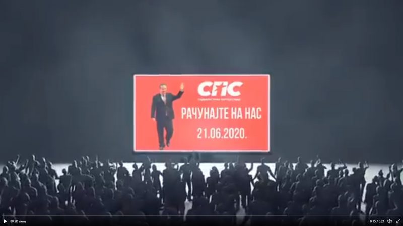Une foule de silhouettes grises se dirige vers une grande affiche rouge, sur laquelle apparait un homme politique en train de saluer.
