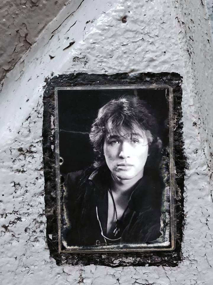 Sur un mur d'hommage, en gros plan, on distingue le portrait du chanteur, sous la forme d'une photo, intégrée au mur. La photo est en noir et blanc, encadrée d'un large trait noir sur le mur blanc.