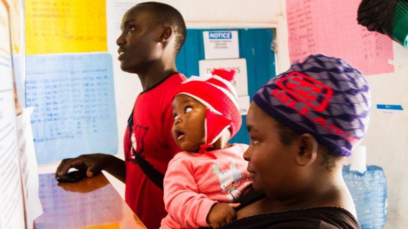 Un jeune couple avec un bébé consultent les bulletins d'information affichés sur les murs d'une clinique à Nairobi, au Kenya.