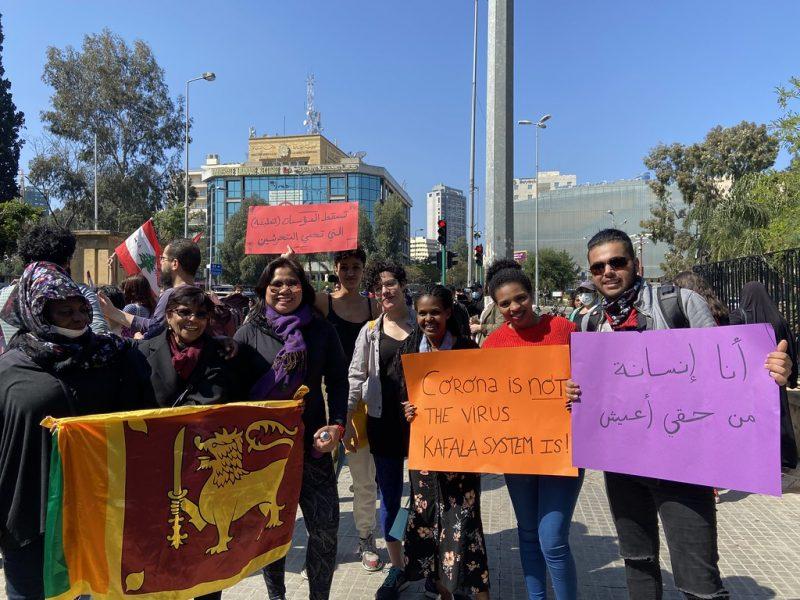 Une manifestation anti-kafala, par une journée ensoleillée. 7 personnes font face à l'objectif, des hommes et des femmes portent des pancartes avec des revendications, écrites en anglais et en arabe. Des personnes brandissent le drapeau du Sri Lanka.