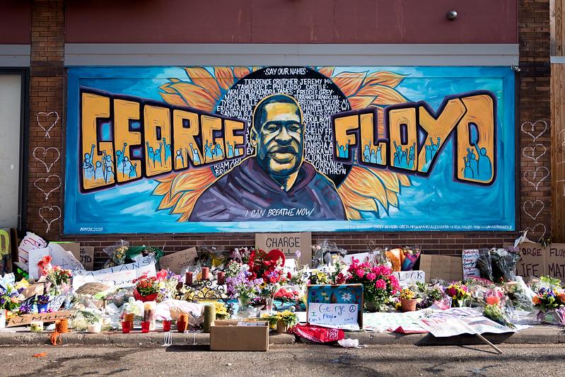 Des gerbes de fleurs jonchent le trottoir devant la fresque. On y voit l'image de George Floyd, entouré d'un halo noir portant les noms d'autres victimes de violences policières.