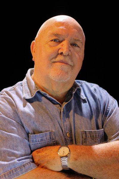 L'auteur Brian S. Heap pose les bras croisés sur la poitrine. Il est de forte carrure, le crânce chauve, et arbore un demi-sourire.