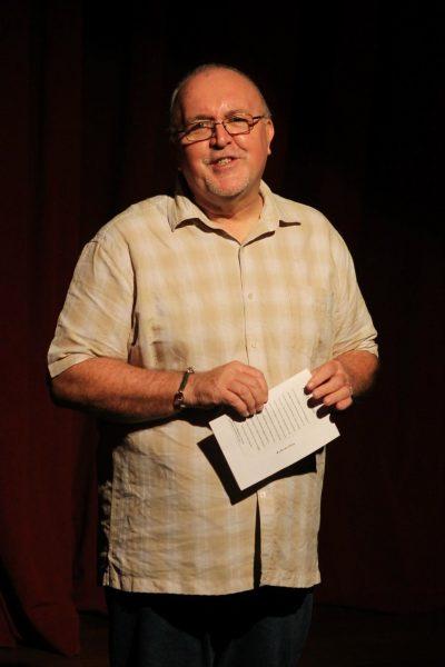 Portrait de l'auteur Brian S. Heap sur fond noir. Il porte une chemise à carreaux et tient dans la main un livret.