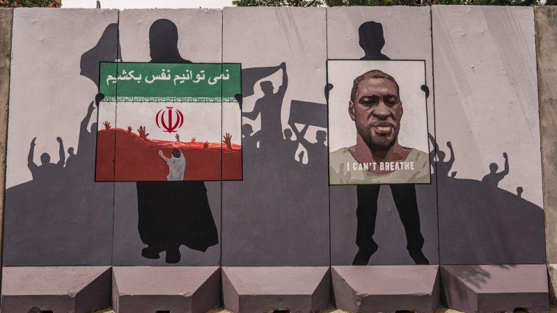 Peinture murale représentant les ombres des manifestant.e.s, le poing levé. Un drapeau iranien apparait en couleurs en regard d'un portrait de George Floyd.