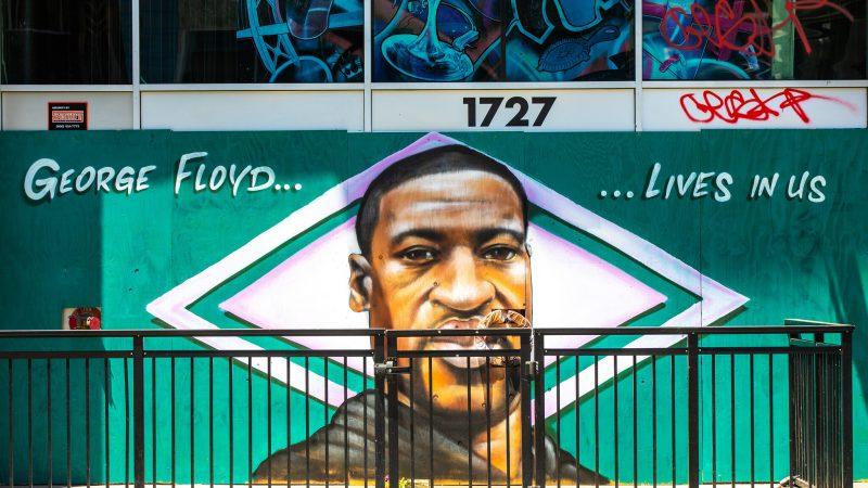 """Fresque montrant le visage de George Floyde avec, de part et d'autre, le slogan : """"George Floyd... Vit en nous."""""""