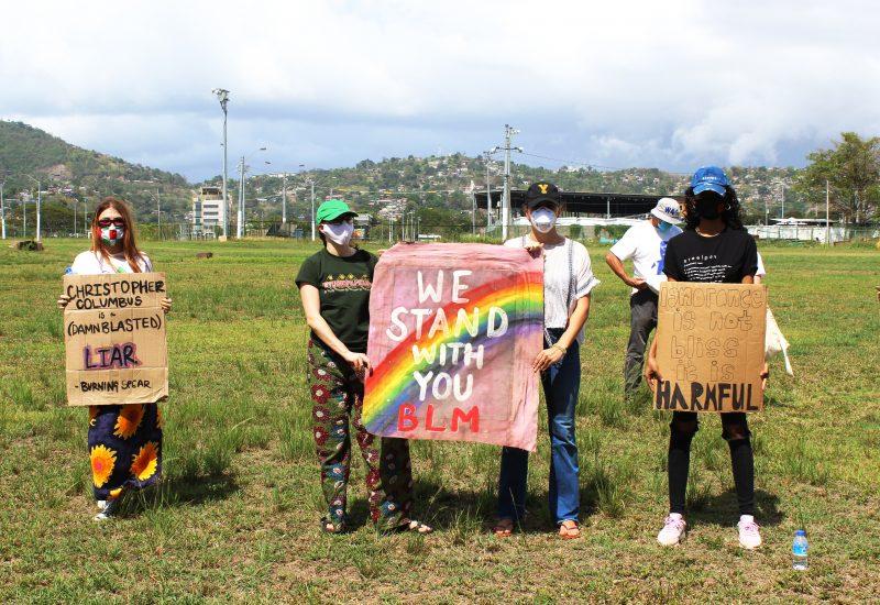 Quatre manifestant·e·s tiennent des pancartes faites maison portant des slogans en solidarité avec BLM. Chacun·e porte un masque.