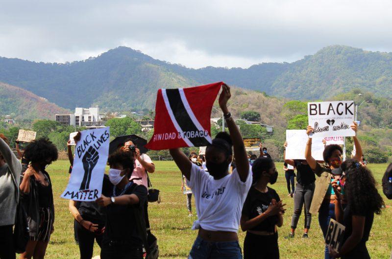 """Les manifestant·e·s brandissent des pancartes """"Black Lives Matter"""" et le drapeau de Trinité-et-Tobago."""