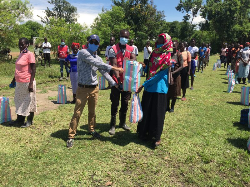 Dans un parc au Kenya, une femme reçoit un paquet de la part de l'ONG Towa Kitu Kidogo, tandis que d'autres attendent leur tour.