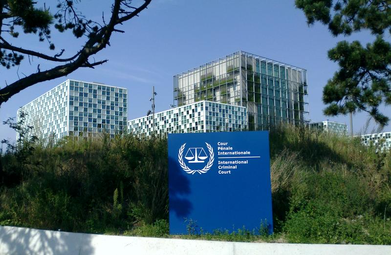 Panneau à l'entrée de la Cour pénale internationale, portant le logo de l'organisme. Les bâtiments, bleu et blanc, ont des formes carrées.