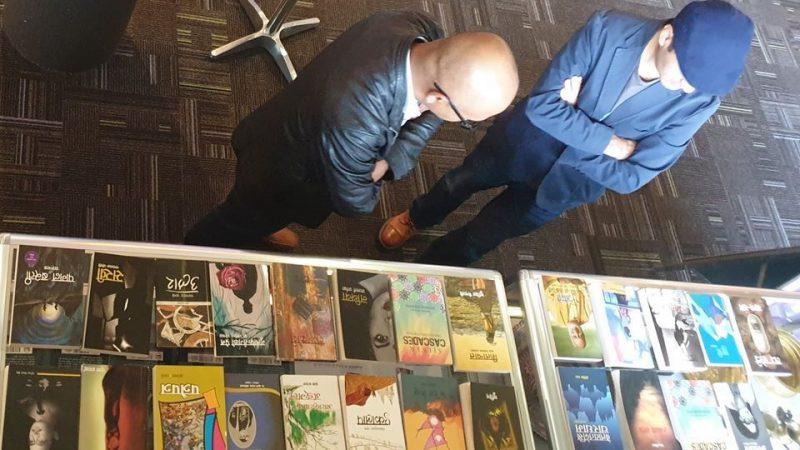 """Vue plongeante sur deux personnes consultant un étal de livres lors de l'exposition """"Nepal Yatra"""" au Royaume-Uni."""
