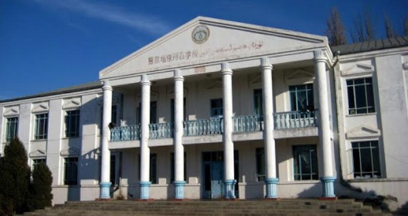 Il s'agit d'un établissement scolaire de couleur blanche, avec un étage et de larges fenêtres. On distingue un balcon bleu au niveau de l'entrée. On y accède par des escaliers. La porte d'entrée est bleue et, sur la façade avancée, on peut voir le nom de l'établissement. Une rangée d'arbres est visible sur le côté gauche du bâtiment. Le ciel est bleu.