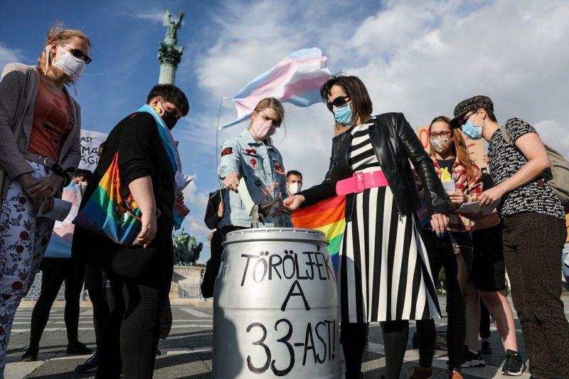 """Un groupe de manifestant.e.s portant des masques faciaux insère des papiers dans un tonneau marqué """"article 33"""". On peut voir des drapeaux trans et arc-en-ciel."""