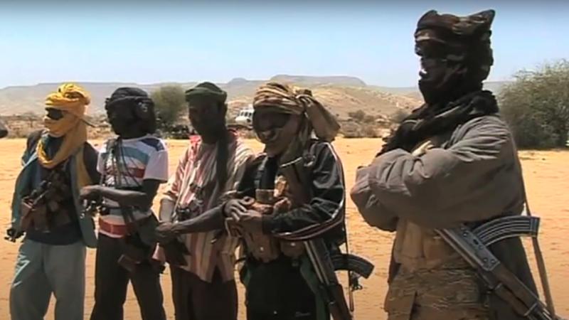 Des membres de Janjaweed se tiennent les bras croisés sur la poitrine, fusil à l'épaule. Leurs visages sont cachés par des turbans.