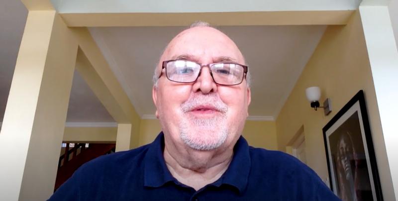 L'auteur Brian S. Heap pris en photo depuis une caméra d'ordinateur. Il a une courte barbe blanche et porte des lunettes à montures rectangulaires.