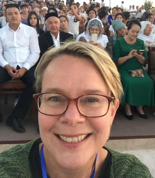 Selfie de Rachel Harris, souriante. Elle est blonde et porte des lunettes. Derrière elle, on distingue une assemblée de personnes assises, des hommes et des femmes.