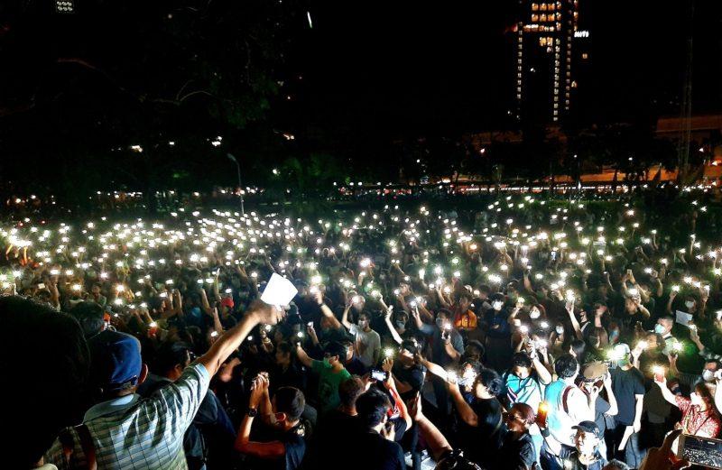 Une marée de lumières dans la nuit laisse deviner une immense foule.