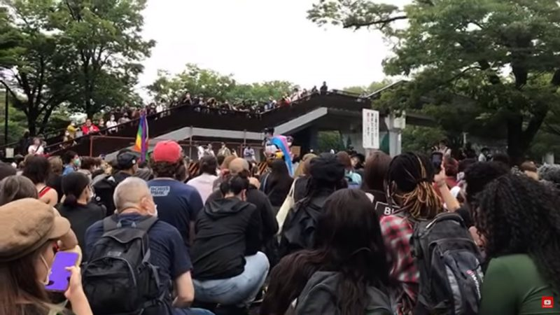Une foule compacte marche contre le racisme à Tokyo. On distingue au fond un drapeau arc-en-ciel.