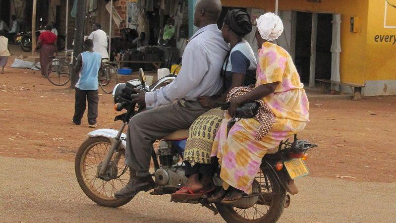 Deux femmes passagères et un conducteur, de dos, traversent un marché sur une moto-taxi en Ouganda.