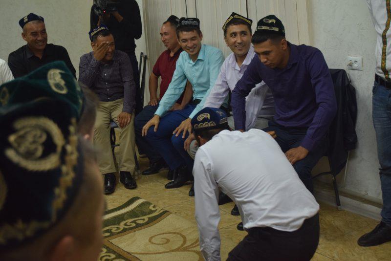 Une réunion d'hommes, la plupart assis et quelques uns debout. L'un d'eux est à genoux sur un tapis, les autres semblent plaisanter et rire face à lui.