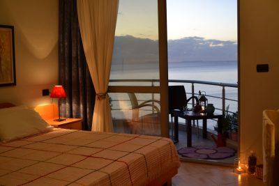 Une chambre d'hôtel au Seaside Artist, avec balcon et vue sur la mer.