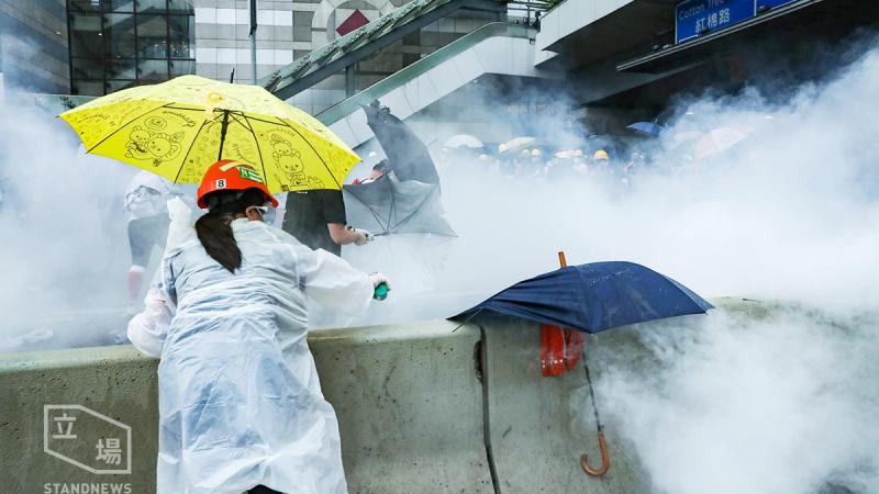 Une femme de dos portant un imperméable blanc et une casquette rouge fait face à un nuage de gaz lacrymogènes.
