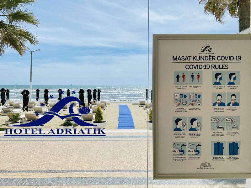 Vue de la plage à travers la porte vitrée de l'hôtel Adriatik en Albanie. Les mesures de protection contre le COVID-19 sont affichées, bien en évidence.