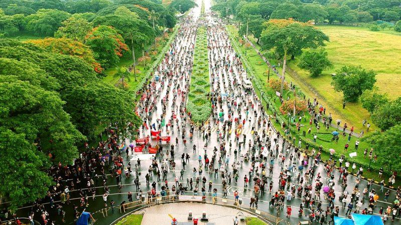 Sur l'avenue de luniversité, entourée d'espaces verts, une foule de manifestants est espacée à cause des mesures de distanciation sociale liées au COVID.