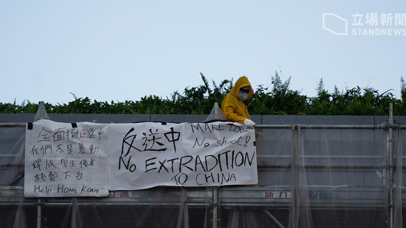 Uun homme vêtu d'un imperméable jaune, portant un masque de protection faciale et des gants blancs, se tient debout sur un échafaudage. Il pose une banderole sur laquelle on peut lire des inscriptions en chinois et en anglais.