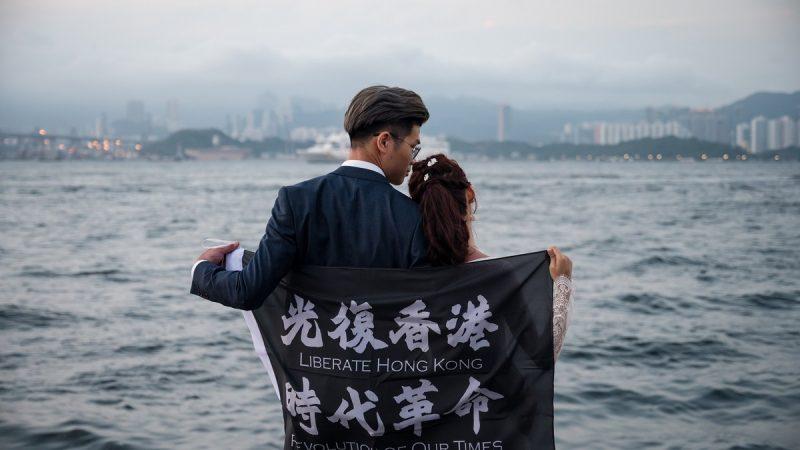 """Un couple de mariés, lui en costume et elle, dans une robe blanche, apparaissent de dos. Tous les deux tiennent une banderole sur laquelle on peut lire """"Libérez Hong Hong, Révolution de notre époque""""."""