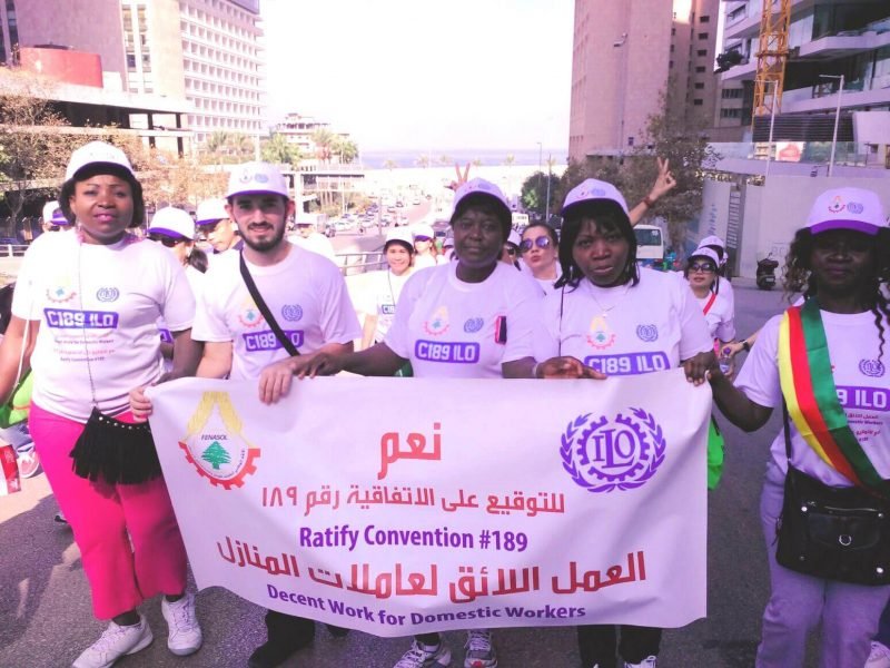 Des personnes défilent dans les rues de Beyrouth. Elles représentent les travailleurs domestiques migrants. 5 personnes tiennent une banderole avec des inscriptions en anglais demandant de meilleures conditions de travail. Elles portent toutes une casquette à cause du soleil.