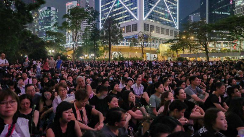 Au premier plan une foule de femmes avec l'air très sérieux, assises dans un parc le soir. Quelques arbres les séparent d'un groupe de bâtiments illuminés.