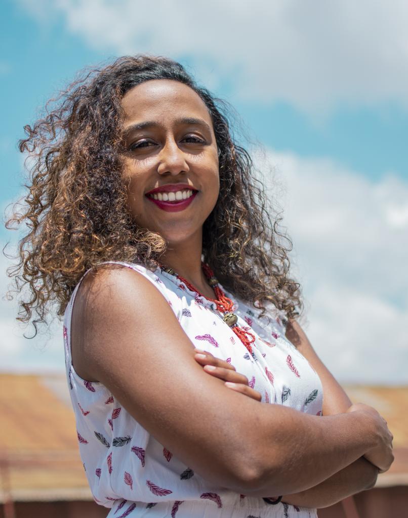 Portrait de Neema Iyer, bras croisés sur la poitrine, souriante.