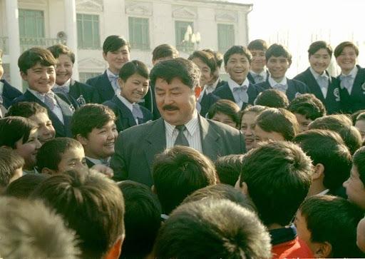 On distingue un homme en costume cravate, avec une moustache brune. Il est entouré par de jeunes garçons, écoliers. Tous sont souriants. La scène se situe à l'extérieur, devant l'établissement scolaire.