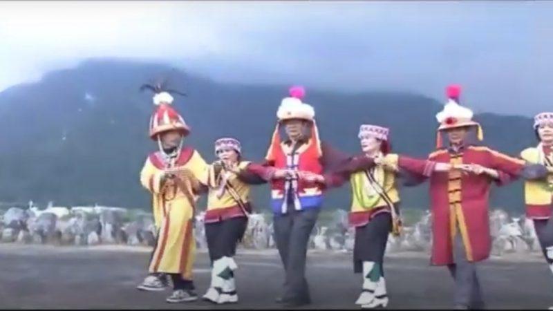 Des hommes et des femmes en vêtements traditionnels sakizaya exécutent une danse en se tenant par la main.