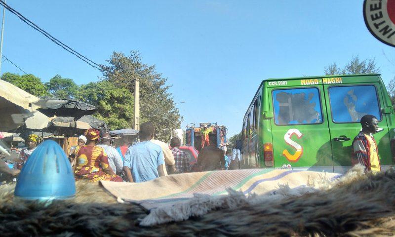 Une rue encombrée de Bamako, vue depuis le pare-brise d'une voiture. Des piétons circulent entre les véhicules.