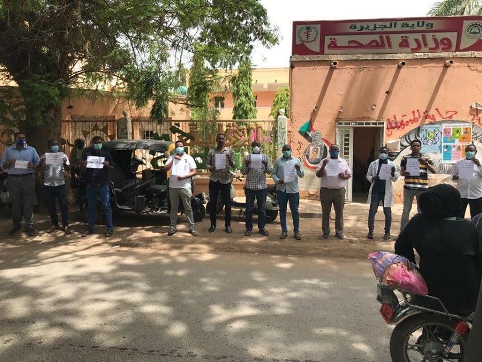 Protestation des pharmaciens soudanais dans l'État d'Aljazeera. Debout, formant une ligne, ils portent de petites pancartes blanches.
