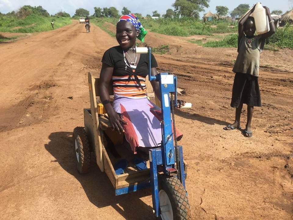 Une jeune femme handicapée dans un fauteuil roulant en bois sur une piste en OUganda